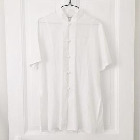 763412c5400 Kortærmet hvid skjorte bluse med Kina krave og knapper. Har slidser i  siden, hvor