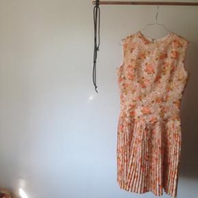 Vintage/retro kjole, i 1950'erne stil med med et mere 1920'erne agtigt snit. Plisseret skørt og blomstret, i en støvet rosa/gammelrosa men har et friskt udtryk med de laksefarvede blomster. Sidder tæt fra hoften og op og ellers løst i skørtet. Passer en str s,