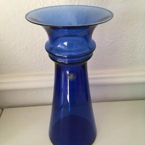 Elegant flot blå vase Crystal fra Royal Copenhagen i perfekt stand sælges. Højde 28 cm. Passer perfekt til et veldækket bord med stel fra Royal Copenhagen.  Se også mine andre spændende annoncer, da jeg bl.a. sælger ud af min glassamling.