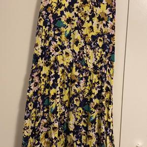 Gul blomstret kjole. Har elastik på midten, og er kort til medium længde. Alt efter din højde. Har kryds på ryggen og skøn som en let sommerkjole/strandkjole.