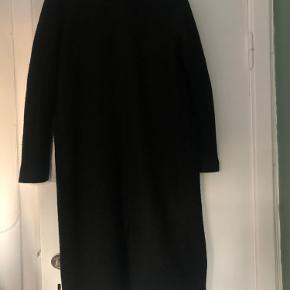 Lang sort frakke fra Monki. Er lidt fnulret, men det er ikke noget man lægger mærke til. Indeholder 38% uld.