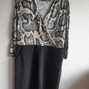 Super smart og behagelig kjole med slangeskindsmønstret slå-om overdel i sand og sort og glat sort underdel med sidelommer. En klar favorit til kontoret eller en tur i byen.  Længden er lige under knæet.