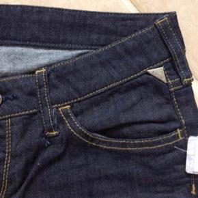 """Varetype: Nye fede jeans fra Replay. Replay Jeans med 3/4 ben. Farve: Blå Oprindelig købspris: 1400 kr.  Rigtig fede NYE jeans fra Replay And Sons.  Jeg syntes de har et fedt snit og fede detaljer. Benene stumper lidt, hvilket er moderne for tiden, hvor man også ruller dem lidt op.  Fede sommer og forår, men også vinter, til støvler.   Der står """"32"""" og """"142 cm"""" inde i dem.  MÅL:  Hvis du kigger på billedet af livet, så går de ned i en """"trekant"""" foran, hvilket giver en større livvidde end målt lige over.   Lige over bagpå = 35 cm. Hver """"spids"""" = 19 cm x 2 = 38 cm Hvis jeg ligesom forsøger at få """"trekanten op i vandret, syntes jeg de måler 2x38 cm, men jeg ved ikke om det er helt præcist.   Indv. Benlængde: 62 cm. Udv. Benlængde: 82 cm.  Når de ligger fladt på bordet og måler fra skridt og op, måler de 20 cm. Bemærk de går ned i et V foran, så jeg vil tro de sidder under navlen foran og går så op i siden ved hoften. Fra skridt og op til talje bagpå måler de 28 cm. Stoffet er med strech.  NP: 1400,- Mp: 250,- pp Bruger helst Mobilepay   Se også mine andre annoncer."""