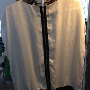 Varetype: Bluse Farve: Råhvid  Smuk bluse med sort flæse foran og lynlås bagpå.