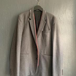 Brand: Kris Van Assche Varetype: Wool blazer Størrelse: L/XL Farve: Grå Oprindelig købspris: 8500 kr.  KRIS VAN ASSCHE sports blazer i grå uld med rød/hvid trim ved revers og håndled, samt hvid kontrast materiale under kraven        Har været brugt 1 gang.        Det er en fransk str 54 men i et slim fit, så passer mere en L den en standard XL.