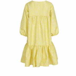 Super fed kjole fra Mads Nørgaard... Den har et blomstret jacquard mønster, der er lavet i en blød polyester. Designet har en v-halsudskæring, 3/4 ærmer og et stort skørt med en række læg. Pasformen er oversize.... Aldrig brugt... BYTTER IKKE...