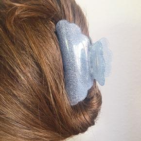 Stor glimrende hairclaw hårspænde / hårklemme i lyseblå med glimmer. Brugt en enkelt gang, men sælger mine farvede hårspænder,  da de ikke passer til min hårfarve længere, efter at have farvet det:) Måler cirka 11cm og god kvalitets clips - vist på min søster, som har ret tykt hår og det kan sagtens holde det hele:)  Kan sendes med dao igennem tradono-handel for 31.95kr (1-2 dage) eller postnord uforsikret og ikke-sporbar for 10kr (5 dage) - sporbar med postnord for 20kr. Kan også afhentes i malling.