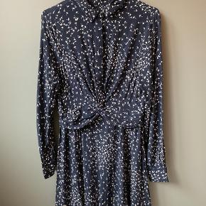 Ganni kjole i modellen Barra. Kjolen har en twistdetalje fortil og er i et fint blomsterprint. den har elastik i taljen og gemte knapper fortil.