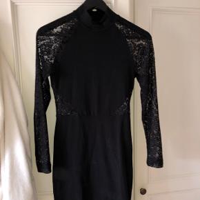 Sort kjole med detaljer ved taljen og ærmerne
