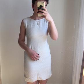 Hvid vintage kjole med mønster i stoffet. Der følger et tilhørende bælte med. Den lynes i siden. Passes af en størrelse XS/S.