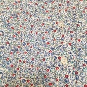 Fin vintage skjorte fra Cacharel i 100% bomuld med Liberty blomster print. I god vintage stand uden huller , pletter, fnuller eller lign. Der står 42/12 i skjorten men den er lille i str. Jeg er selv en dk 36 38 og passer den. Tjek gerne mål: Brystmål: 47 cm på tværs fra armhule til armhule dvs 94 cm i omkreds. Længde: 59 cm fra nakken og ned. Søgeord: skjorte bluse småblomstret blomstret blomster lyseblå rød mint grøn retro vintage print mønster mønstret bomuld