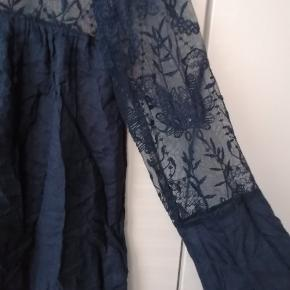 Pæn løs bluse, med blomstret tyndt stof omkring toppen af ryg og bryst.