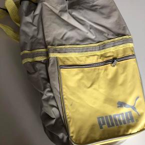 Lysegrå/gul retro taske fra Puma. Tasken har en lille lynlåslomme på ydresiden og har et stort rum, der lukkes med snøre. Derudover har tasken to justerbare stropper, så den kan bruges som rygsæk.