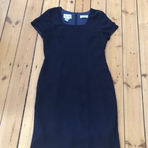 Flot, figursyet kjole i mørkeblå fra Karin Stevens.  Knælang, lynlås i ryggen og lille slids.   Kan sendes eller afhentes i Rødovre.