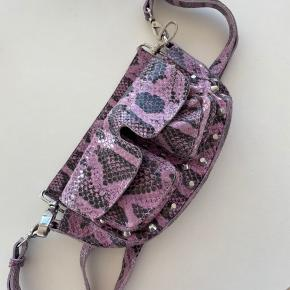 Adax cross-body taske i en fed lilla farve med slange print. Den er ikke brugt ret meget så er næsten som ny. Nypris 999 kr.