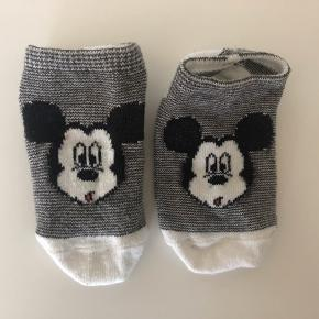 Sokker i str 19-20 med fine Mickey mouse motiver. Uden pletter, misfarvninger, huller mm. Der kan forekomme fnuller på sokkerne, men det er svært at undgå med bomuld.  Fra dyrefrit, røgfrit og parfumefrit hjem. Vasket i neutral. Prisen er 5,- pr. par