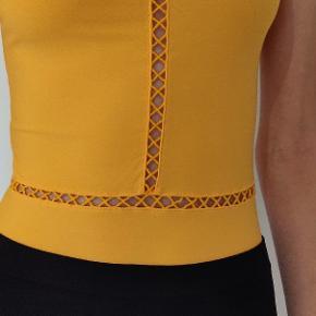 Body I stretch polyester, aldrig brugt. Farven er gul, ikke orange.