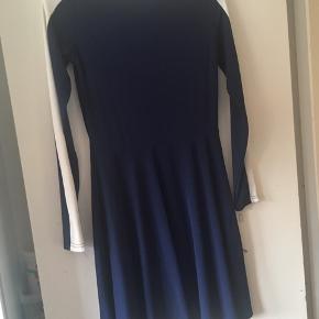 Flot kjole med bådudskæring. Hvid kant i halsen og ned langs ærmerne.
