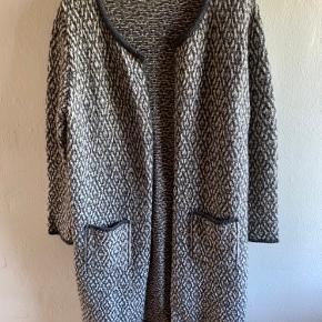 Lækker lang cardigan med lommer. Brugt få gange. Farverne grå og hvid mønstret. 30% New wool 12 % Alpaca 47 % Polyacrilic 11 % Polyamide