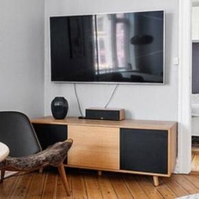 Tv-møbel / skænk / kommode i egefiner til salg.   Møblet har fire låger på hver side (dvs. at man kan vende møblet som man vil). De to yderste låger har har en hylde hver indvendigt.   Tilhørende er låger på hver side. Et sæt i ege finer og et sæt i stof, så man f.eks. kan have højtaler inde i kommoden. Man kan også vælge at blande lågerne, hvilket kan ses på det ene billede.  Mål:  B: 161 cm H:60,5 cm D:55,5 cm  Sælges grundet flytning.  Det er et kvalitetsmøbel, men vi kan ikke huske mærket.   Centerhøjtaleren (gale) er også til salg.