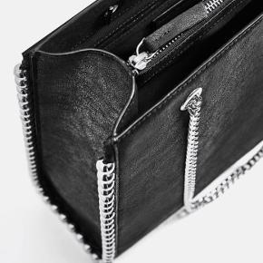 Sort shoppertaske med kædeskulderrem og metalkugler rundt i kanten af tasken. Flere rum hvor det ene har lynlås.  Mål: 32cm x 26cm x 7cm  Afhentning i Valby