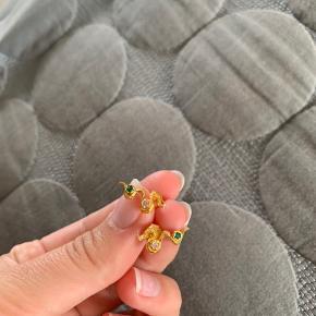 DER ER BUDT 200kr🌶🌶 Kun brugt en gang, æske medfølger ikke💞  KALIAH EARRINGS  Inspireret af havets foranderlighed og elegante bølger bevæger Kaliah øreringen sig med lethed op af øret. Øreringen er fattet med to glitrende zirkoner.  Højde: 7 mm, bredde: 17 Materiale: Sterling sølv (925) belagt med 18 karats guld, rosa og grønne zirkoner.