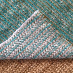 Turkis tæppe med striber af grøn og guld. Stoffet er tykt og rug men mærkes blød mod huden.  Har ikke været i kontakt med røg eller dyr og befinder sig helt uden fejl/patina.  Kan benyttes både som plaid, sengetæppe og gulvtæppe da stoffet er slidstærkt.   133cm bred 194cm lang