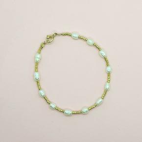 Armbånd med ferskvandsperler og 24 karat guld belagte miyuki perler. Perlerne måler ca. 4 mm i diameter. Armbåndet måler 17 cm, men kan laves efter mål.   Kan afhentes gratis i Odense.