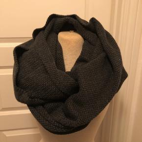 Tubetørklæde i strik. Farven er mørkegrå og strikket er groft.  Byd :-)
