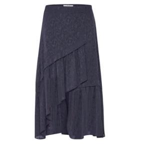 Varetype: Nederdel Farve: Mørke blå Oprindelig købspris: 999 kr.  Nederdelen er aldrig brugt, jeg har købt den for en måned siden men har fortrudt. Den kan også passes af en str 36. Beskrivelse: Nederdel med et asymmetrisk snit og brede flæsekanter foran. Skjult lynlås i siden.  100% polyester