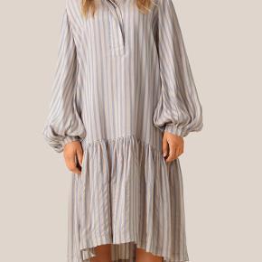 Skøn oversize offwhite kjole med lyseblå striber fra Second Female. Kjolen har midi længde med et smukt skirt forneden, skjult indvendig lomme i siden og lange ærmer med balloneffekt samt skjult knaplukning i halsen.   Mål str M:  Bryst omkreds: 100 cm  Længde: 109 cm