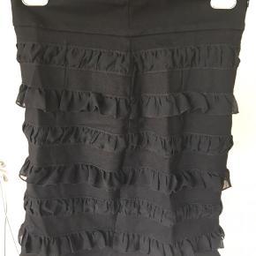 Fed stram nederdel med små flæser. Den kan bruges hvor den sidder både højt og normalt. Der er lynlås i siden. Den måler 52 cm. Der er syning, der er gået bagpå men ikke hul.