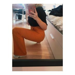Lange orange habitbukser fra Astrid Olsens kollektion med na-kd. De er i størrelse 38, og er brugt få gange.