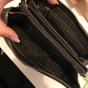 Sælger denne flotte Adax pung i mærkebrunt læder. Den har nogle fine detaljer af nitter på den ene side, og er ellers i rigtig fin stand. Intet slid eller noget. Pungen er dejlig rummelig med plads til telefon op til en iPhone plus.  Er åben for bud - køber betaler fragt.