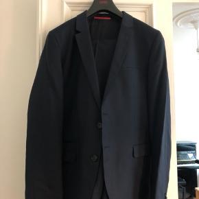 Hugo Boss jakkesæt i mørkeblå i lækkert vævet stof - brugt under 5 gange. Jakke og bukser str. 54. Model: Super 100.  Nypris: 3300kr Original pose og bøjle medfølger.
