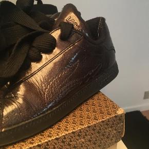 Varetype: Sneakers Farve: Ukendt  Et par fede Lacose sko sælges, farven er lidt svær at beskrive, nærmest gylden sort( se ift sort snørebånd) ikke brugt meget, men får dem bare ikke brugt. TS gebyr ligges oveni samt Porto (33,00) Mener NP ca 800,00 original æske medfølger