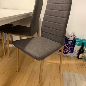 4 flotte spisebordsstole i grå, med brune træben. En 5 stol haves, men den er en meget lille smule mørkere end de andre fire, så den kan man få med gratis hvis det ønskes.