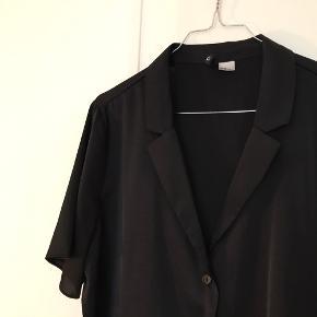 Boxy bluse/kortærmet skjorte. Er kort i længden.