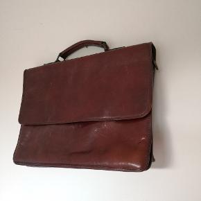 Mappe Super lækker lædertaske i brun/rødbrun. Retro look.  Den har været brugt som jobtaske/computertaske.  Indeholder to fyldige rum samt et rum med lynlås. Udvendig på bagsiden er ligeledes en lomme med lynlås. Skulderremmen er desværre blevet væk men den fungerer fint uden.  Mål: 26x36cm  Den har brugsspor, men fremstår stadig rigtig fin.  Nypris var Ca 2300kr