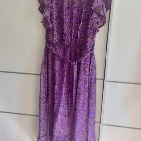 Maxi kjole med flotte ærmer og flæsedetaljer på bryst og forneden. Bindebånd og elastisk talje. Lukkes med knap i nakken.  Flot lilla farve med orange mønster.