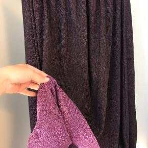 Lang nederdel i glimmer-stof. Lilla på ydersiden og pink indvendig. Elastik i taljen.