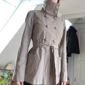 Beige jakke med bindebånd i taljen.  Brugt en enkelt gang til en særlig anledning.