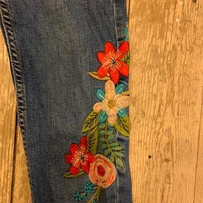 Et par jeans med broderede blomster.