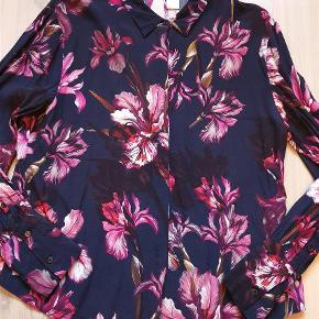 """Brand: MbyM Nord Varetype: skjorte Farve: Mørkeblå Oprindelig købspris: 600 kr.  Super flot og elegant skjorte fra MbyM nord. MbyM Nord er den lidt mere eklusive linje hos MbyM. Skjorten har et fint """"hul"""" i ryggen, som gør den lidt mere feminim. Kun brugt gange. Farverne er mørkeblå med pink/lilla blomster."""
