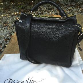 Den smukke taske har en firkantet form, læderrem, indvendig lomme til kort og  i sort læder.  Brugt en gang. Den er ligesom ny. Bredden; 25 cm Højden; 22 cm Dybden i bunden; ca 11 cm Nypris ; 8500 kr