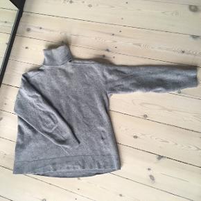 Kort uld bluse med rullekrave, 3/4 ærmer og detalje på ryggen