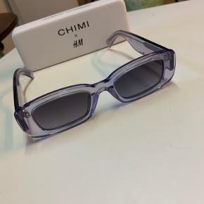 Chimi & HM lyslilla solbriller.  Stel fremstillet af BPA- og ftalatfri celluloseacetat af høj kvalitet.  Glas har UV400 filter, som giver øjet 100% UV beskyttelse.  Stænger og front sat sammen med et hængsel i rustfrit stål.  Etui, pudseklud og pose medfølger.   Total bredde 14.5 cm.   Aldrig brugt.