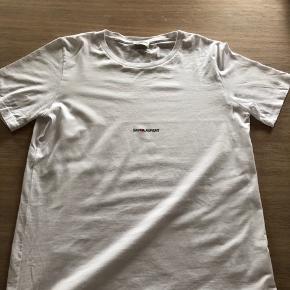 Lækker t-shirt fra Saint Laurent. Købt i sommerferien, men brugt meget få gange. Ingen huller eller pletter. Sælger da jeg mangler penge.