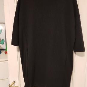 Sort kort kjole/tunika i kraftigt stof med 2/3 lange ærmer. Vaflet/mønstret overflade foran og bagpå med glat stof i siderne. Skrålommer. 81% polyester/18% bomuld/1% elestan.  Mål Længde: 87cm Bryst: 60cm Bundkant: 54cm
