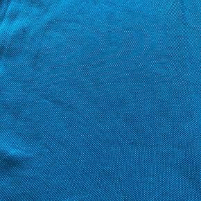 Blå/turkis polo fra Lacoste. 2 små trådudtræk forneden af blusen. Ikke forsøgt ordnet. Ellers fin og brugt lidt.